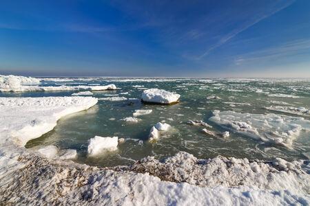Frozen ice ocean coast and blue sky - polar winter