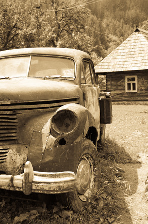 Old retro rusty vintage car and old house photo