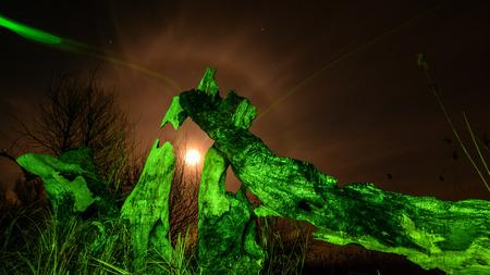 Burned tree -in green light at night full moon,stars and mystyc landscape