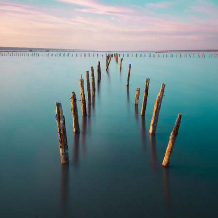 Poles in the water, on sunset clouds and ocean- calmness and silence concept