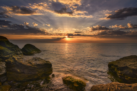 Beautiful ocean sunrise - calm sea and boulders  with sky sun rays and clouds Stock Photo