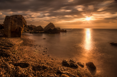 Beautiful ocean sunrise - calm sea and boulders stone coastline with unusual light Stock Photo