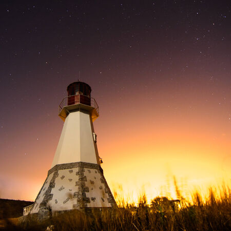 lighthouse with beam to night sky at background stars trails Stock Photo