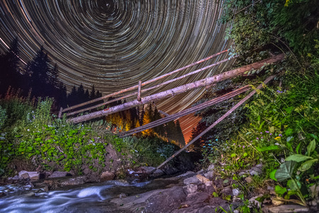 Old bridge on mountain river - night sky startrails