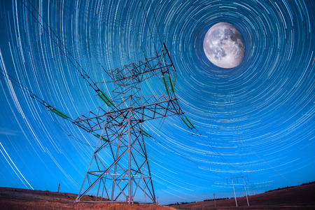 Electricity power poles on night sky and startails moon