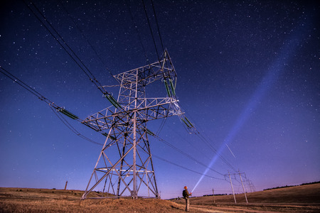 Electricity power poles on alone man -  night sky and stars background