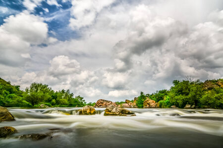 Beautiful river flow with sky stormy clouds, boulders in moving water - long exposure photo