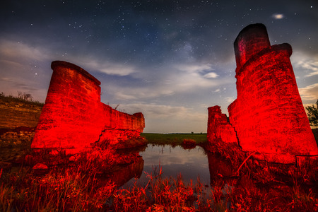 Old night castle wall ruins on lake reflections with stars sky