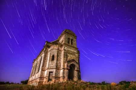 The old church flying in star trails background