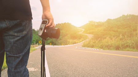 Man holding a camera standing on the street in mountain road  .A traveler or photographer taking pictures on the road trip.