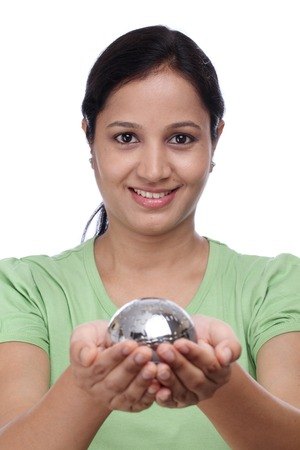 Young woman holding metal jigsaw puzzle globe against white photo