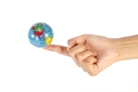 finer: Hand holding a globe on index finer over white .