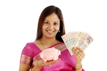 Young smiling Indian traditional woman holding currency and piggy bank over white background  photo