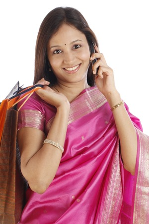 Young Indian traditional woman with shopping bags and talking on cellphone  photo
