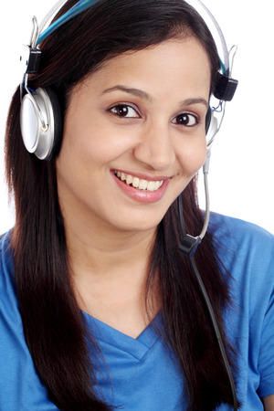 Happy young Indian call center girl against white background photo