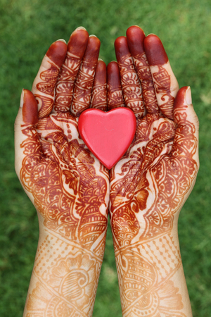 Red heart shape in henna hands  photo