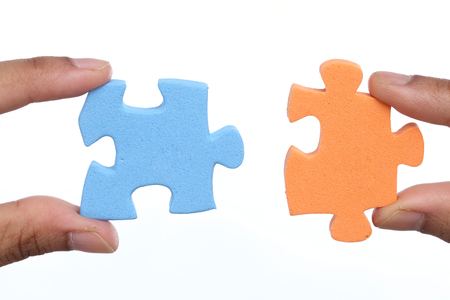 attach: Hands trying to attach two jigsaw puzzle pieces on white background Stock Photo