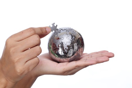 Hand building puzzle globe on white background photo