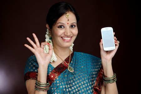 Traditional young woman holding cell phone and making OK sign photo