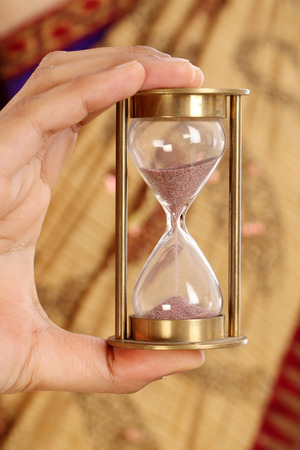 A woman hand holding a hourglass  photo