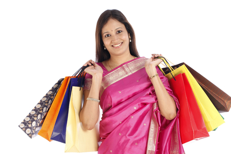 Happy young Indian traditonal woman with shopping bags photo