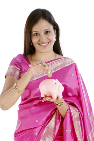 Young Indian traditional woman inserting a Indian ten rupee coin  in a piggy bank  photo