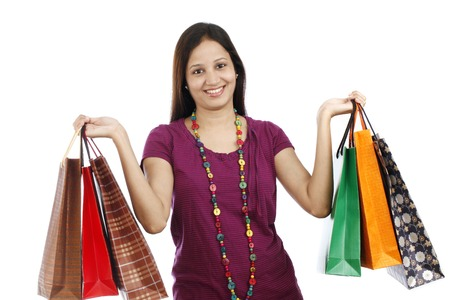 carrying girl: Happy young Indian woman holding shopping bags isolated on white background Stock Photo