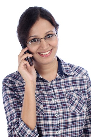 Young woman talking on a mobile phone against white background photo