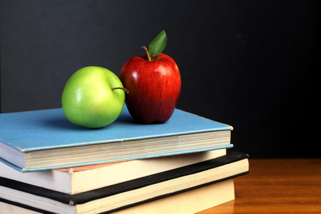 Red and green apple on text books Stock Photo