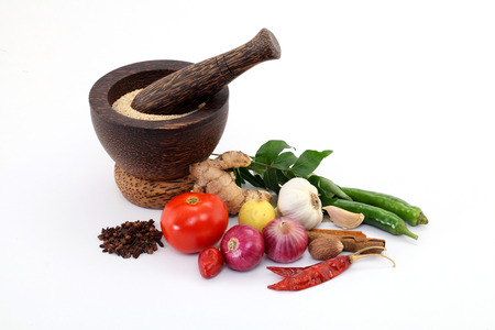 Wooden mortar with various spices on white background photo