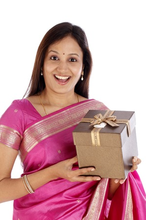Surprised young Indian traditional woman holding gift box against white background photo