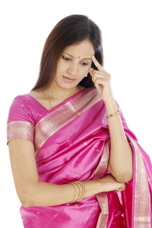 Stressed young Indian traditional woman against white background photo