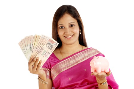 Smiling Indian traditional woman holding currency and piggy bank over white background  photo