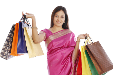 Happy young Indian traditional woman with shopping bags  photo