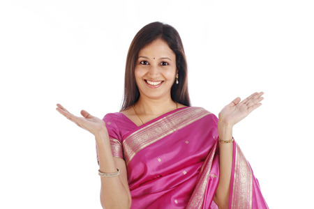 Excited young Indian traditional woman against white background photo