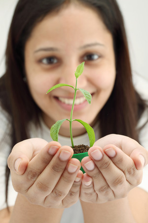 Closeup of young woman holding young plant in her hands  photo