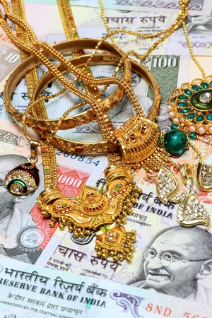 Gold ornaments on Indian currency photo