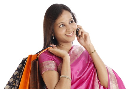 Happy Indian traditional woman with shopping bags and talking on cellphone  photo