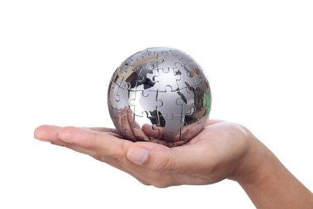Hand holding metal puzzle globe on white background photo