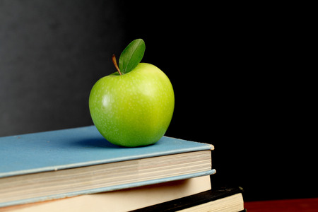 Stack of exercise books and green apple  photo