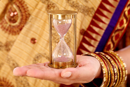 Woman hand holding a hourglass  photo