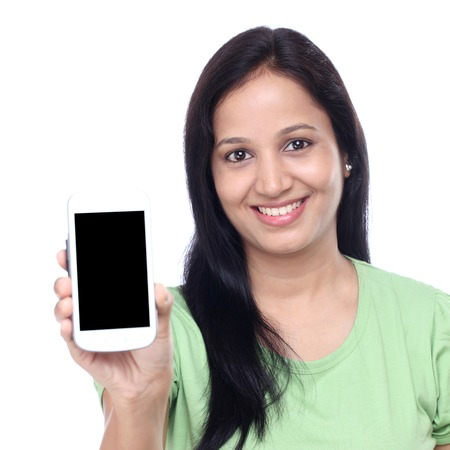 Smiling Indian woman showing display of mobile phone with blank screen Stock Photo