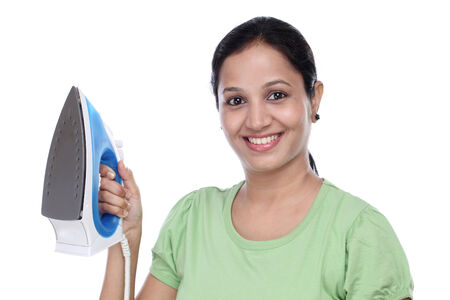 Happy young woman holding steam iron against white background photo