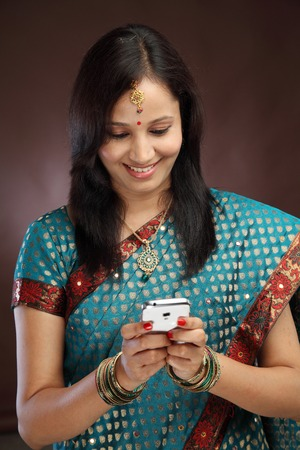 Smiling young traditional woman text messaging photo