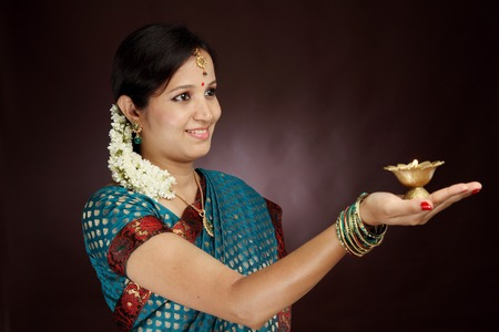 Traditional young woman holding diwali diya photo