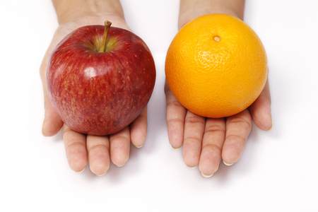 front raise: One apple and orange on woman hands isolated on white