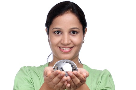 Happy young woman holding jigsaw puzzle globe against white photo