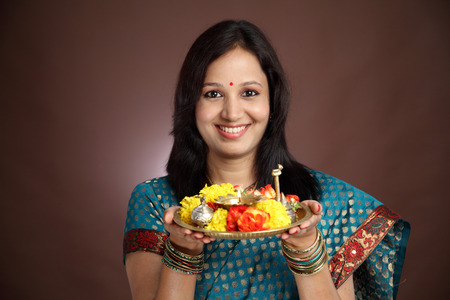 Smiling young traditional woman holding a plate of religious offerings photo