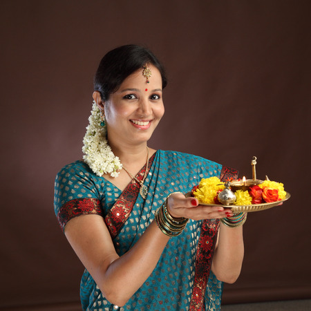diya: Smiling young traditional woman holding a plate of religious offerings Stock Photo