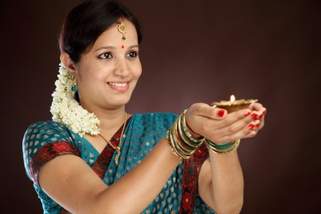 Young traditional woman holding diwali deepam photo